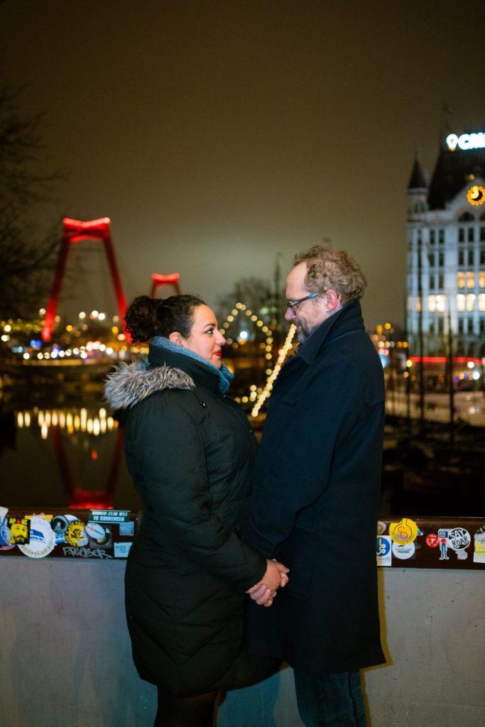 Paul en Amoorah poseren bij nacht in de Oude Haven in Rotterdam. Op de achtergrond zie je de Willemsbrug en het Witte Huis.